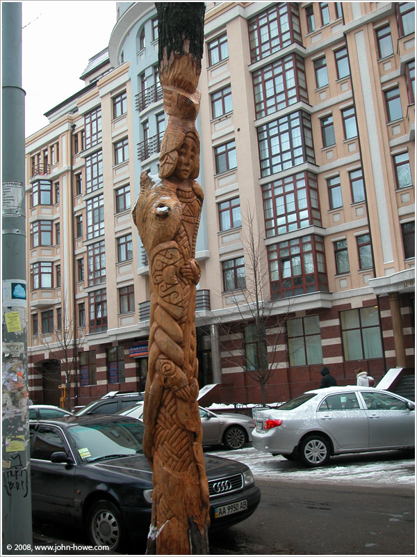 We are in Kyiv, Ukraine, looking at a rich brown tree carved into the image of a warrior in the Ukrainian/Slavic tradition. In the background is a side street filled with parked cars and building fronts.