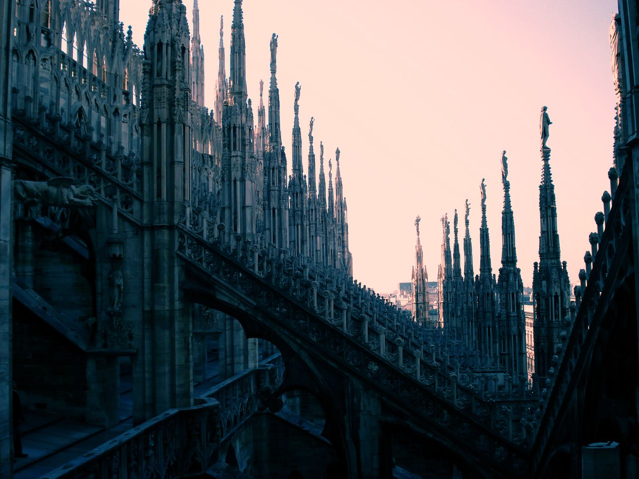 The Gothic architecture of the Duomo di Milano: flying buttresses and ornate towers in profile, lined up in ranks stretching into the distance. All is steeped in deep blue shadow against a delicate pink-peach sky.