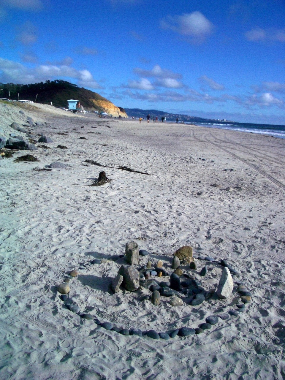 A sandy beach beneath a lightly-clouded blue sky.  In the background is the verdant cliffside of Torrey Pines State Park and hills beyond, with distant figures of beach-walkers and a blue lifeguard shack. At the fore stands a circle made of pebbles, stones arranged inside the circle like some kind of miniature henge.