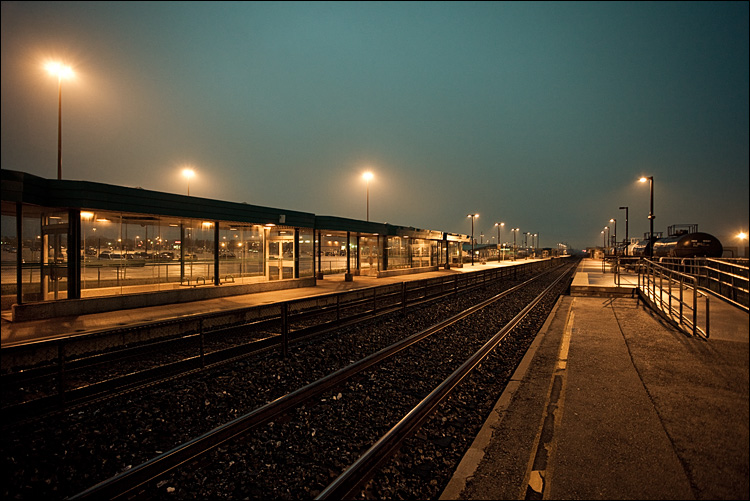 At the platform of a train station, watching the platform and the tracks stretch into the horizon. Yellow floodlights throw bluish shadows upon a foggy sky.