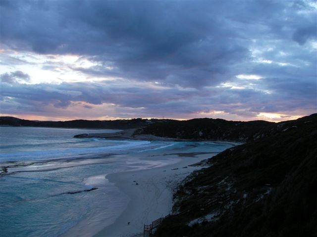 A bay surrounded by dark cliffs. Cold aquamarine surf breaks upon the sandy beach, while dark blue clouds cover the sky, and a distant sunset turns the horizon into a line of yellow fireglow.