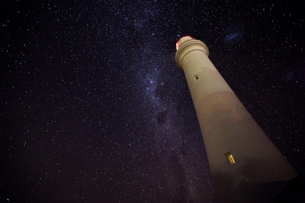 Photograph. A lighthouse rises into the night sky, flanked by the Milky Way and a host of glittering stars.