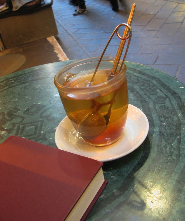 Photograph of a large clear mug on a white dish, the ball infuser stuck into it, steeping a rich golden herbal tea. The table on which the mug rests is green stone with a scrollwork design. A red hardback novel lies next to the tea mug, ready to be read. In the background are pavement and the feet of passersby.