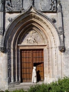 Photograph. A white-robed monk, hood covering his head, enters the door of La Grande Chartreux. He is dwarfed by the splendour of the architecture.