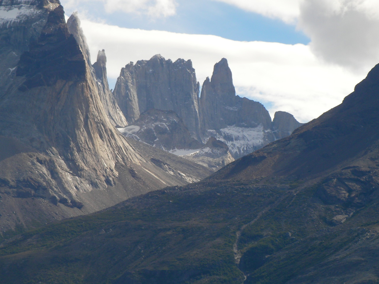 Photograph. Rugged granite mountains, rise into the cloudy sky in jagged toothy ridges in the Torres Del Paine National Park. Their grey flanks are bare of vegetation, and white snow lingers in the shade.