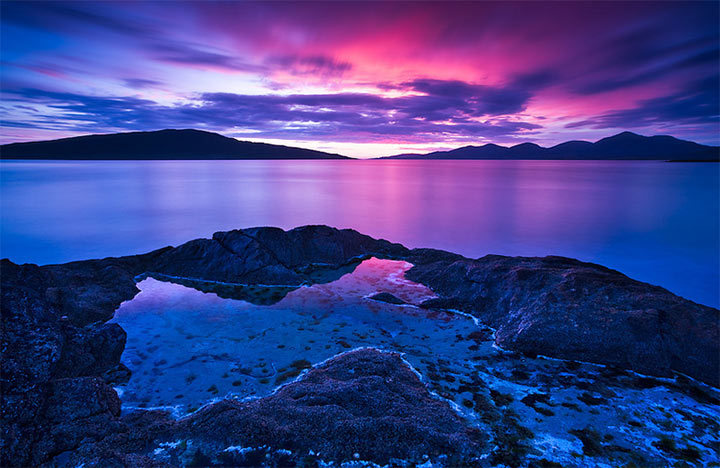 A rocky shore and lagoon, stretching into still, glassy waters.  Hills loom on the other shore, the sun setting between them, casting light past a dark cloud cover. All is swathed in shades of blue and purple.