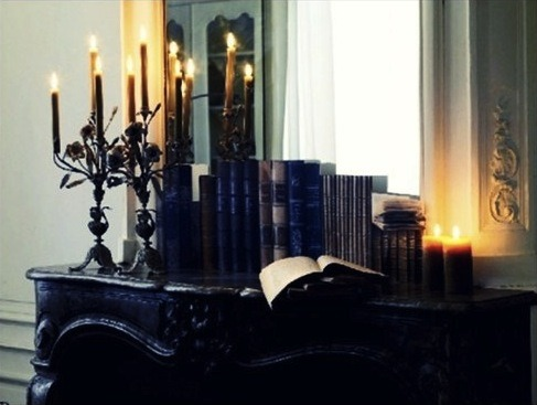 On a dresser, old books stand in a neat row, flanked on the right by two column candles, on the left by two candelabra, all lit with warm flames. In front of that shelf lies an open book, as if the reader had put it down and left it there, forgotten. A mirror behind the dresser shows a window screened by gauzy curtains. Though the scene is brightly lit, the dresser is dark, the candles are warm, and all looks cozy and inviting.
