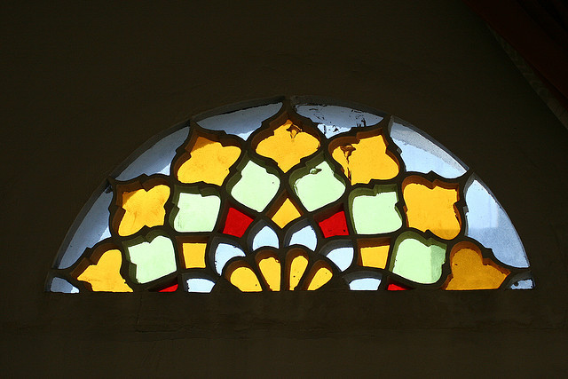 Photograph of a Middle Eastern stain-glassed window, lit at night from within. The window is a horizontal half-moon shape, the segmented panes arranged in the pattern of a Middle-Eastern mandala/flower, each segment coloured in sunflower yellow and the palest green, accented by bright crimson and pale blue. The window shines vivid amidst the dark night.