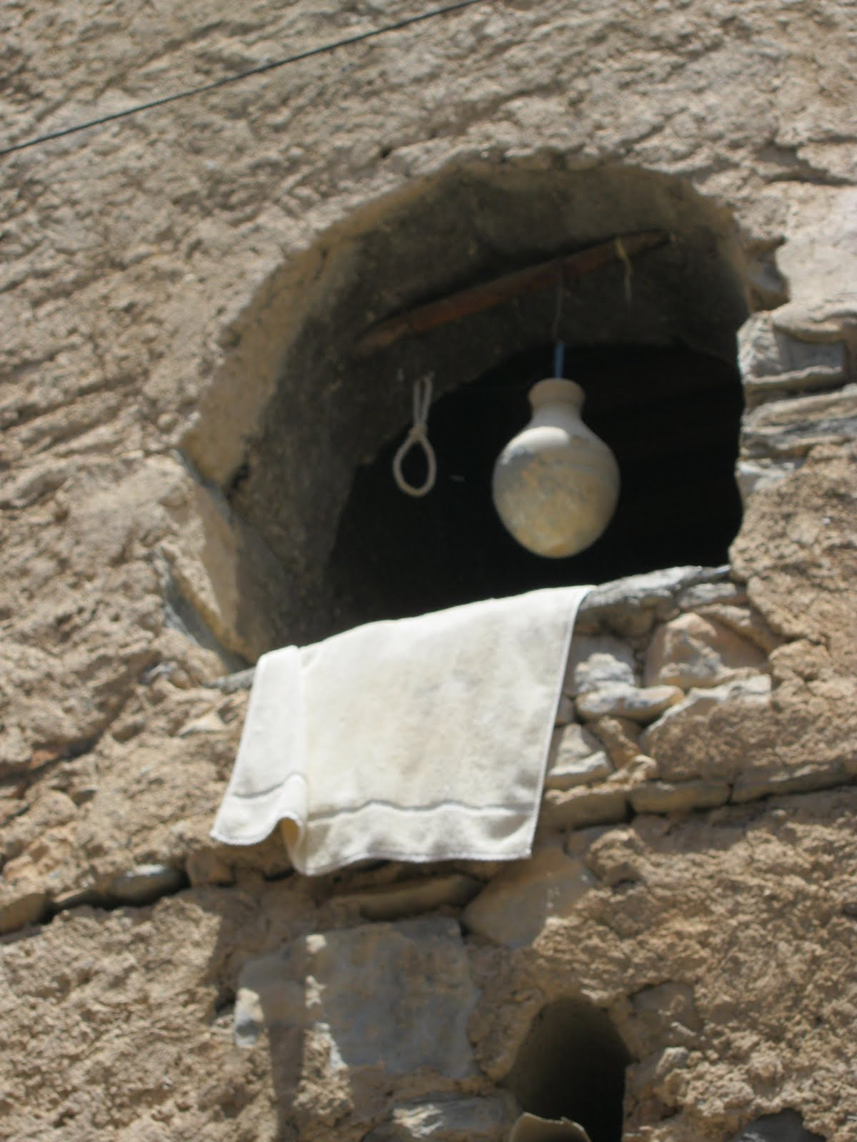Photograph. A round window opens up in a stone wall. A white towel drapes over the ledge. A round, bulbous earthenware water urn hangs suspended from a bar mounted across the top of the window. Next to it is an empty looped rope, awaiting its own urn.