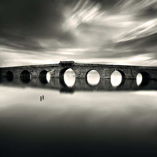 Photograph in monochrome. An arched bridge standing over utterly still waters, its seven symmetrical arches forming perfect circles with their reflections. Two posts stand in the water in front of the bridge as if suspended in mid-air, while cirrus clouds sweep the sky above.