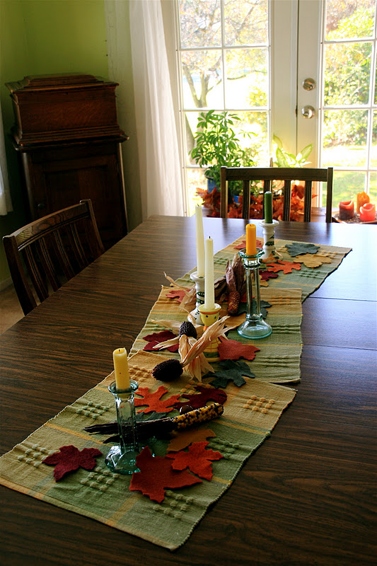 Photograph in a home, of a centrepiece on a wooden dinner table. Earth-coloured tartan placemats, handcrafted fabric maple leaves, pime cones, creamy taper candles in glassss and ceramic candleholders... This centrepiece, coupled with the brown wood of the table, a wooden cupboard, and plants standing before the glass sliding doors in the background, all give a homely, hospitable air in anticipation of the American Thanksgiving.