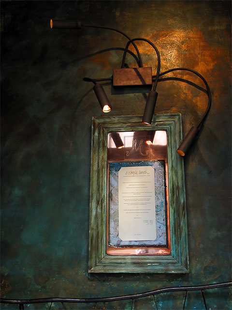 A restaurant menu printed on cream paper with a broad blue swirled border, framed in a picture frame of verdegrised copper. The menu hangs on a wall stained with the same tarnished colour. A trio of goose-necked point-lights shine upon the menu, while a glow of copper light falls upon the wall.