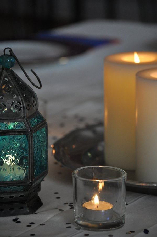 Photograph. A white tablecloth strewn with gold confetti. Atop it stands a green glass lantern, dimly glowing, a tealight in a simple clear glass, and two large pillar candles on a filigree dish. The image is soft, contemplative, and cozy.