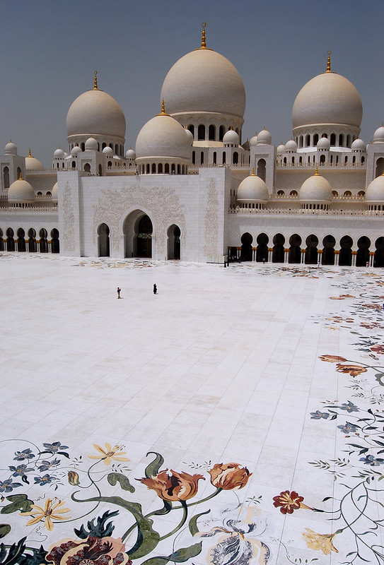 Photograph of a courtyard before a mosque. The mosque is made of pure white stone, with filigree over the arched doorways, and paintings of colourful flowers on the tiles around the courtyard perimeter. The mosque radiates a glorious, beautiful, pristine presence.