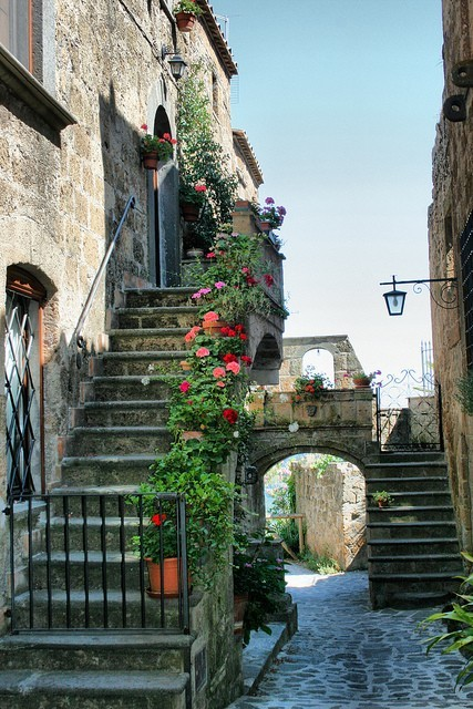 Photograph. A residential lane runs between stone houses with steps leading up to their doors, and through an ornamental stone arch, and beyond. The nearer staircase is barred by a low gate, but potted plants and flowers line the steps all the way to the landing and the doorway beyond. The sky beyond is clear and sunny, giving this idyllic lane a feeling of sunny peace and homely welcome.