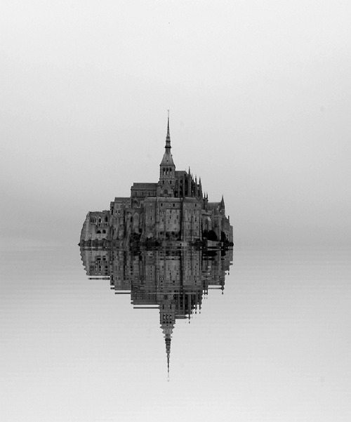 Black and white photograph, possibly digitally edited. An island made of a heap of buildings and a steeple rises from still waters, an edifice grand and lonely in its isolation between water and sky.