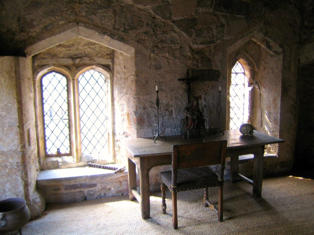 Photograph. The cell, showing two large and barred oriel windows set into the stone wall, with a desk and chair positioned against the wall between them. On the desk are two wrought-iron candleholders, and between them, a wooden sculpture of a crucifix, with Mary holding the dead Christ. Sunlight streams in from the two windows, but the desk is in shadows.