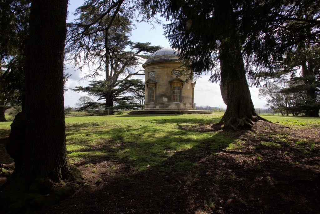 Photograph. An old, weather-worn, stone rotunda standing in a clearing under the sun; seen through the shadows of the nearby trees.