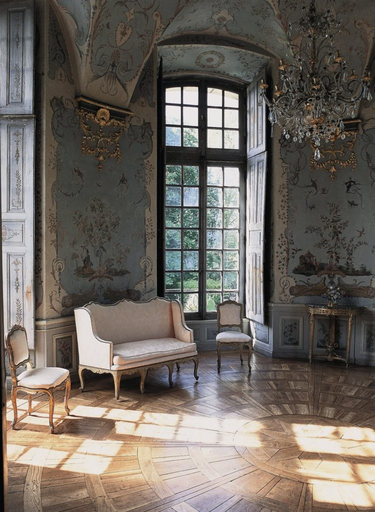 Photograph. Rococo interior of a house. The parquet on the floor is arranged into a radial shape; the couch and two chairs are upholstered in white; the walls are richly decorated in rococo. A floor-to-ceiling window with square panes is set between the walls, and a chandelier hangs  from the ceiling. Sunlight falls into the room, illuminating the floor and the white furniture, a contrast to the cool shadows of the walls and ceiling.
