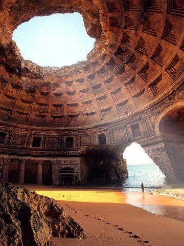 Mixed media photograph?  A giant, free-standing dome straddles the beach, standing half on yellow sand, half on water. The waves rush in through a hole in its wall, while the sunlight streams into the dome from a hole in its roof. A figure stands in the surf, looking out to sea.