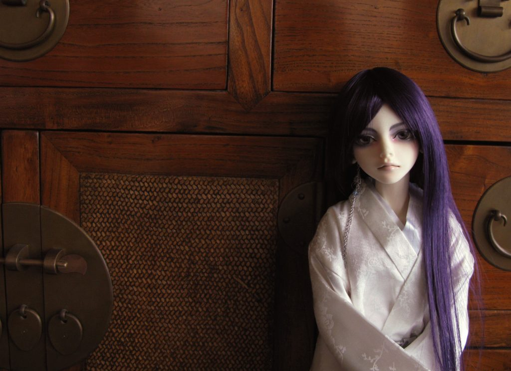 Photograph of an Asian ball-jointed doll (ABJD), leaning against a wooden panelled wall. Robed in a white kimono, arms folded, straight, dark purple hair falling over one shoulder, she stares pensively, maybe wistfully, back at the viewer.